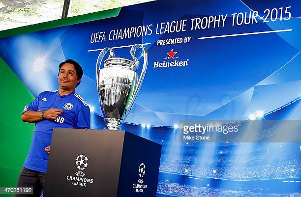 A fan poses with the Champions League Trophy at the 2015 UEFA Champions League Trophy Tour presented by Heineken exhibition on April 18 2015 in...