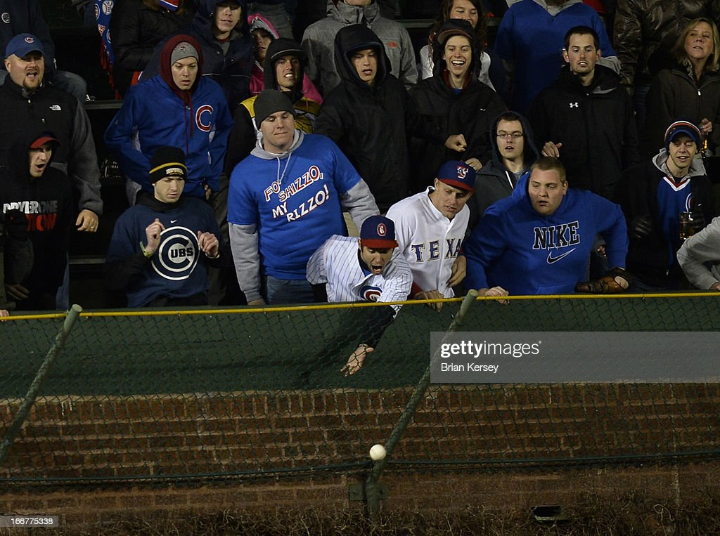 A fan reaches for an RBI double hit by Jeff Baker of the Texas Rangers, scoring Adrian Beltre during the fourth inning against the Chicago Cubs at Wrigley Field on April 16, 2013 in Chicago, Illinois. All uniformed team members are wearing jersey number 42 in honor of Jackie Robinson Day.