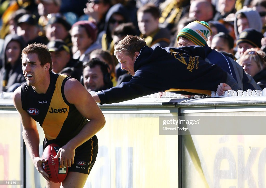 A fan reaches out to touch Daniel Jackson of the Tigers during the round 17 AFL match between the Richmond Tigers and the Fremantle Dockers at Melbourne Cricket Ground on July 21, 2013 in Melbourne, Australia.