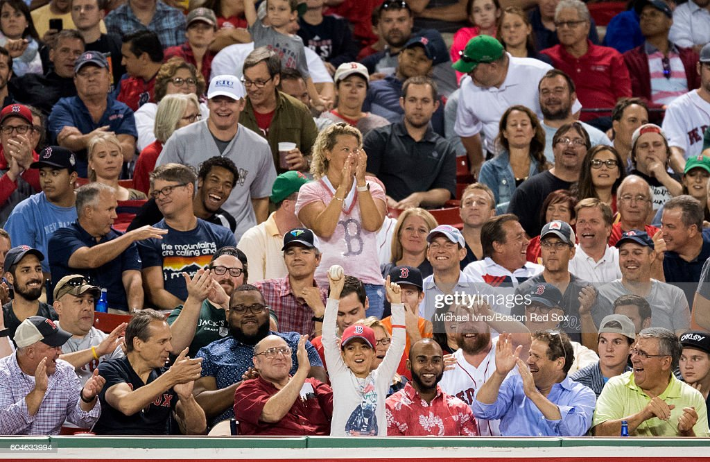 A fan reacts after getting a foul ball during a game between the Boston Red Sox and the Baltimore Orioles on September 13, 2016 at Fenway Park in Boston, Massachusetts.