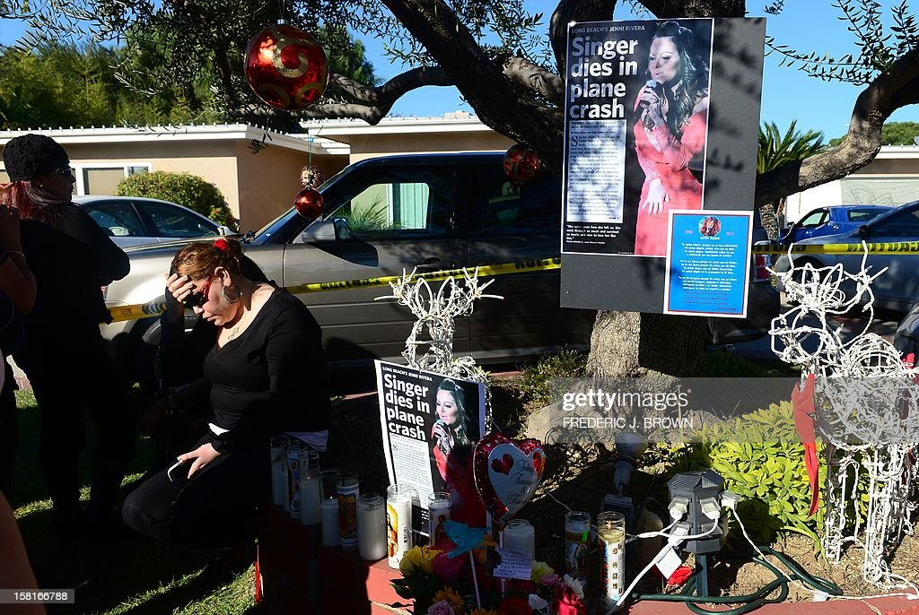 A fan reacts beside a makeshift shrine mourning the death of Mexican-American diva Jenni Rivera in front of her home in Lakewood, California on December 10, 2012, south of Los Angeles. Fans and celebrities are mourning the death of Rivera, a star on both sides of the border, as investigators scoured the site of her plane wreck for clues. The 43-year-old singer was among seven people, including two pilots, killed when their small Learjet plane crashed in rugged terrain in the northern Mexican state of Nuevo Leon early December 9. AFP PHOTO / Frederic J. BROWN
