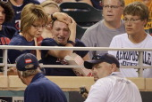 A fan reacts to being hit in the head by a foul ball during the seventh inning of the game between the Minnesota Twins and the Kansas City Royals on...