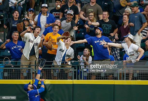 A fan readies to catch a tworun homer off the bat of Mark Trumbo as right fielder Jose Bautista of the Toronto Blue Jays leaps at the wall in the...