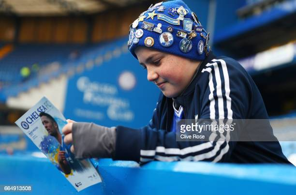 A fan reads the matchday programme inside the stadium prior to the Premier League match between Chelsea and Manchester City at Stamford Bridge on...