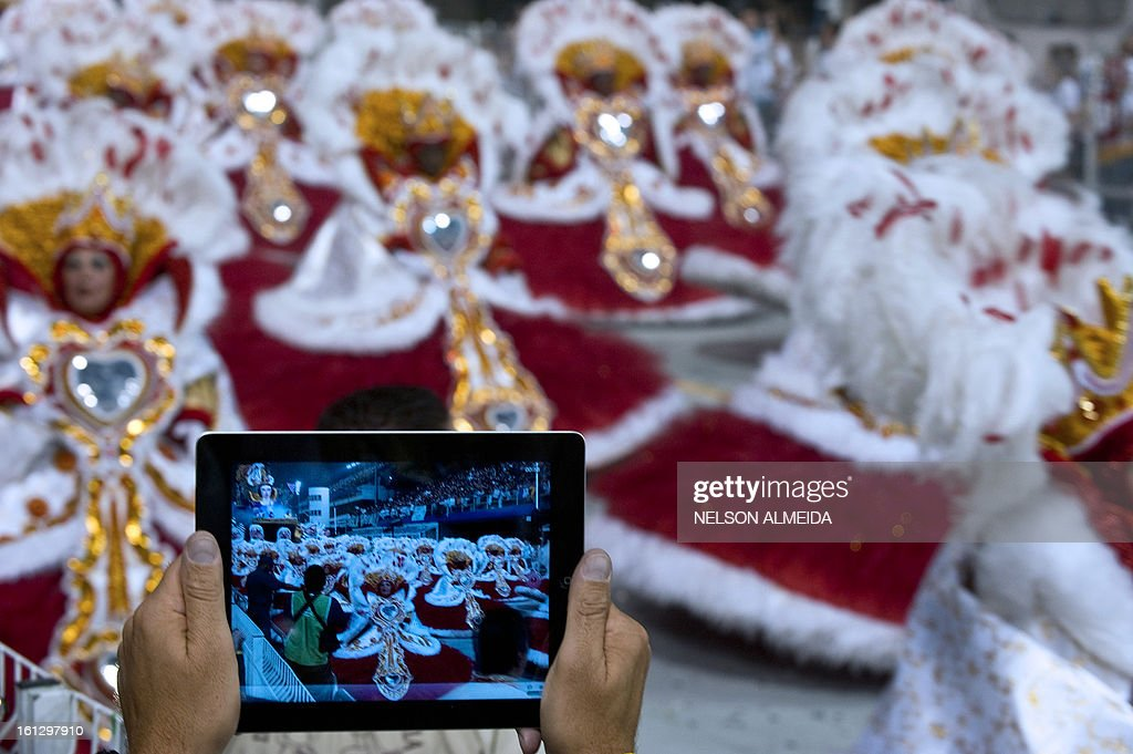 A fan records on his iPad revelers of Mocidade Alegre samba school as they perform during the second night of Carnival parades at Sao Paulo on February 10, 2013. AFP PHOTO / Nelson ALMEIDA