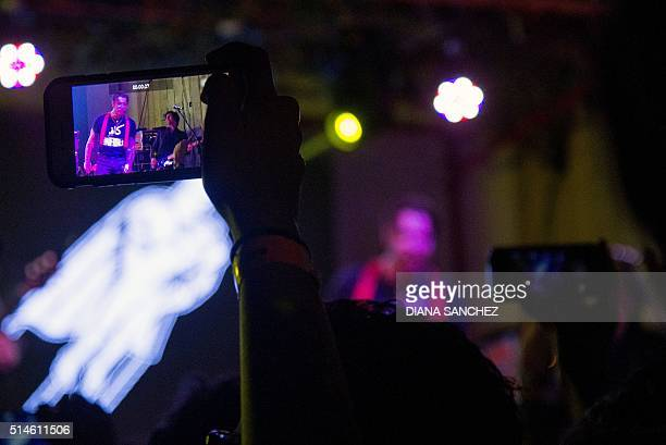A fan records on his mobile phone the band Eagles of Death Metal during a concert in Bogota on March 9 2016 AFP PHOTO/Diana Sanchez / AFP / DIANA...