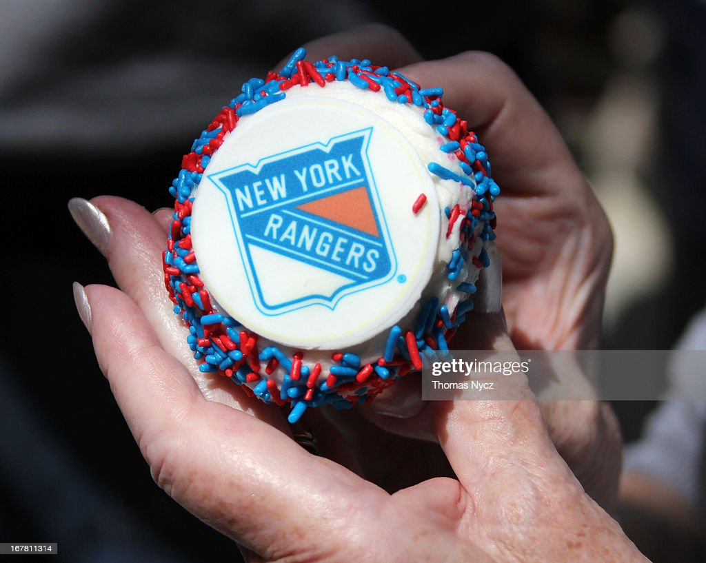 A fan removes the wrapper from a New York Rangers themed cupcake during a 2013 Stanley Cup Playoffs kickoff event at Madison Square Park on April 30, 2013 in New York City. The NHL, NBC Sports and Crumbs Bake Shop hosted the event to celebrate the start of the 2013 Stanley Cup Playoffs.