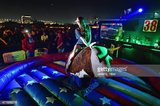 A fan rides a mechanical bull on the infield at Talladega Superspeedway on May 1 2015 in Talladega Alabama