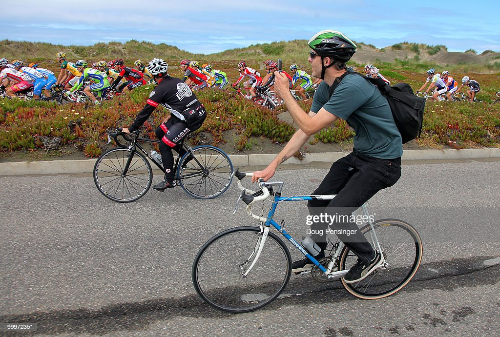 A fan rides his bicycle and takes photos of the peloton as they roll out of San Francisco at the start of Stage Three of the 2010 Tour of California from San Francisco to Santa Cruz on May 18, 2010 in San Francisco, California.
