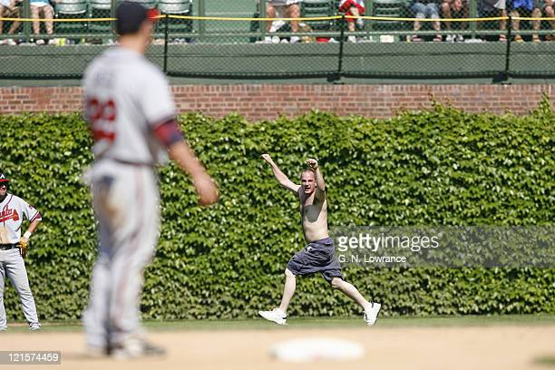 A fan runs on the field during action between the Atlanta Braves and Chicago Cubs at Wrigley Field in Chicago Illinois on May 28 2006 The Braves won...