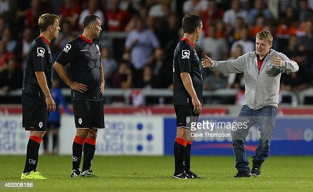 A fan runs on to the pitch to hug Gary Neville during the match between Salford City and the Class of '92 XI at AJ Bell Stadium on August 7 2014 in...