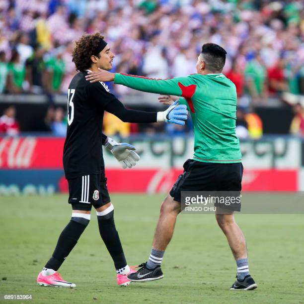 A fan runs onto the field and greets with Mexico goalkeeper Guillermo Ochoa left during the second half of an international friendly soccer game...