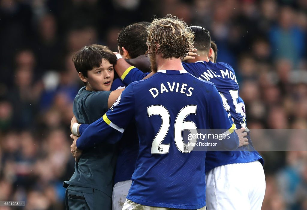 A fan runs onto the pitch to celebrate with goalscorer Romelu Lukaku of Everton (obscured) and players after scoring his sides third goal during the Premier League match between Everton and West Bromwich Albion at Goodison Park on March 11, 2017 in Liverpool, England.