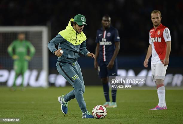 A fan runs with the ball after invading the pitch during the French L1 football match between Paris SaintGermain and Monaco at the Parc des Princes...