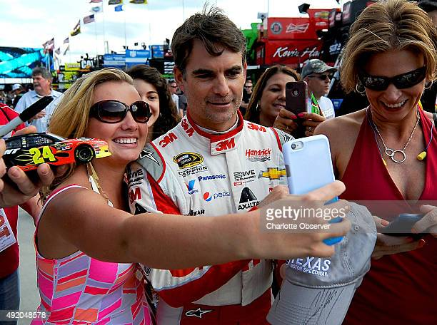 NASCAR fan Savannah Dean left of Akron Ohio smiles as she takes a selfie with NASCAR Sprint Cup Series driver Jeff Gordon right as he walks to his...