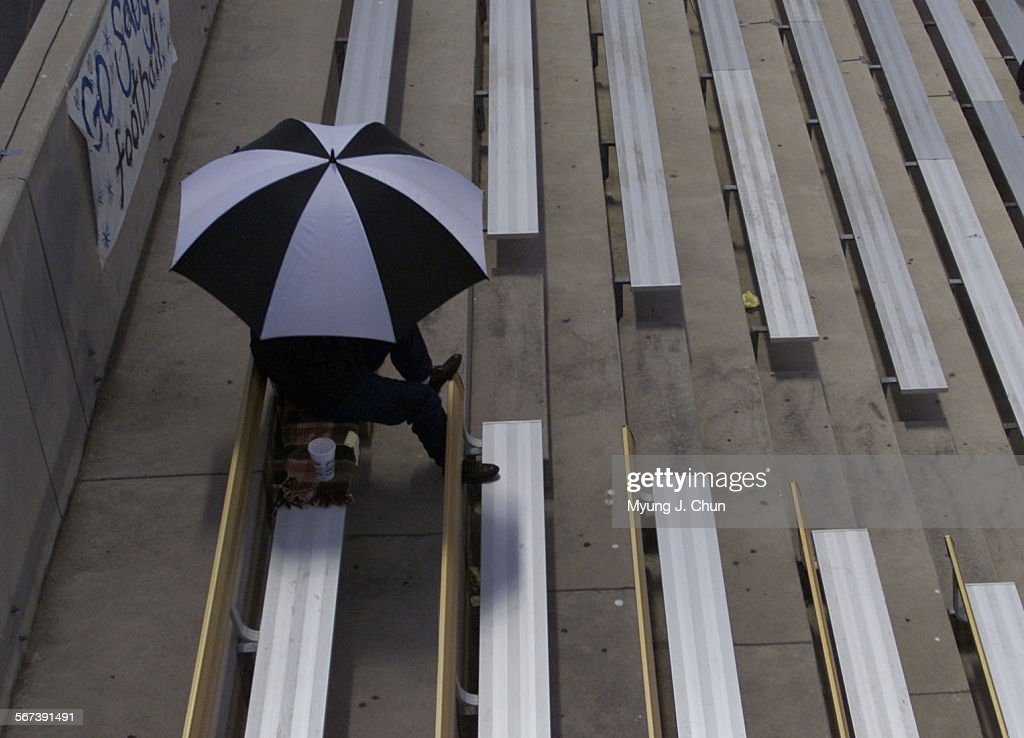 A fan seeks shelter from a light drizzle before the start of the Notre Dame vs Saugus High School game at College of the Canyons on Friday night in...