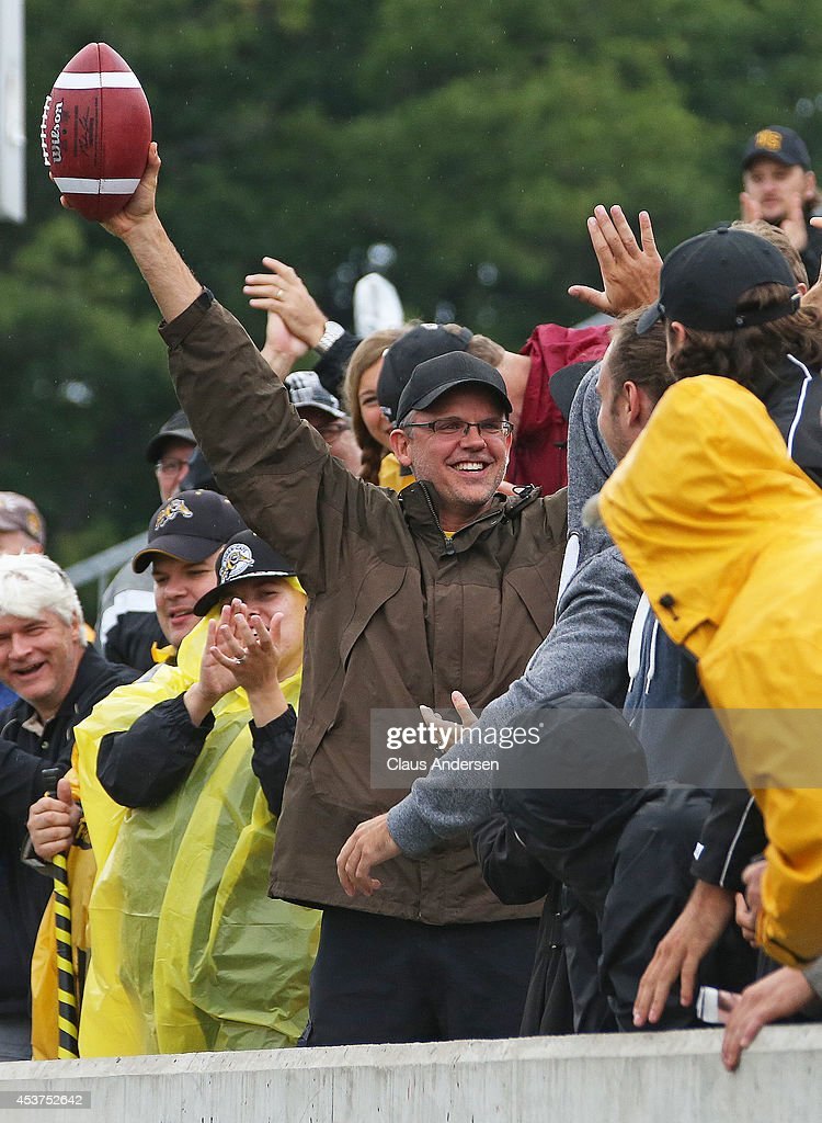 A fan seems pleased with his catch on an errant pass during play between the Hamilton TigerCats and the Calgary Stampeders in a CFL game at Ron Joyce...