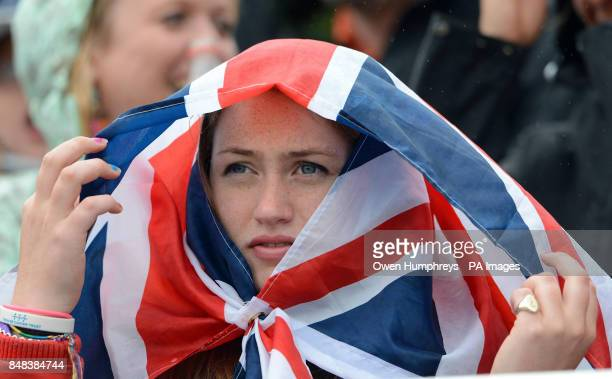 A fan shelters from the rain as she watches the Individual Eventing Jumping Final on day four of the London Olympic Games at Greenwich Park London