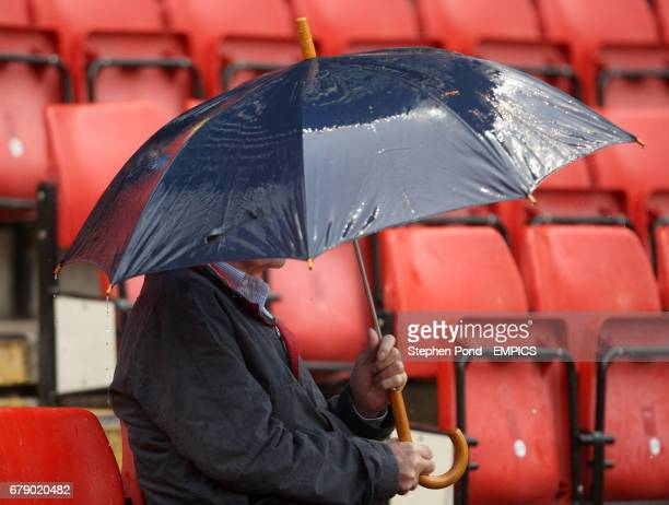 A fan shelters under an umbrella at The Valley as the rain continues to fall