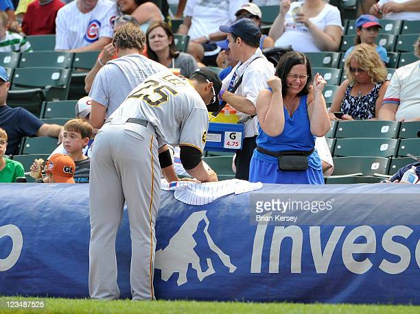 A fan shows her excitement as Derrek Lee of the Pittsburgh Pirates signs her jersey before the game against the Chicago Cubs at Wrigley Field on...