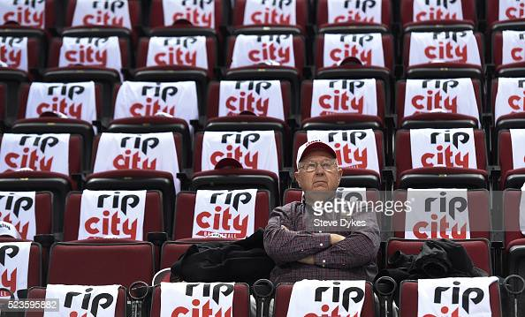 A fan sits in his seat surrounded by free tshirts and hats laid out on the seats before Game Three of the Western Conference Quarterfinals during the...