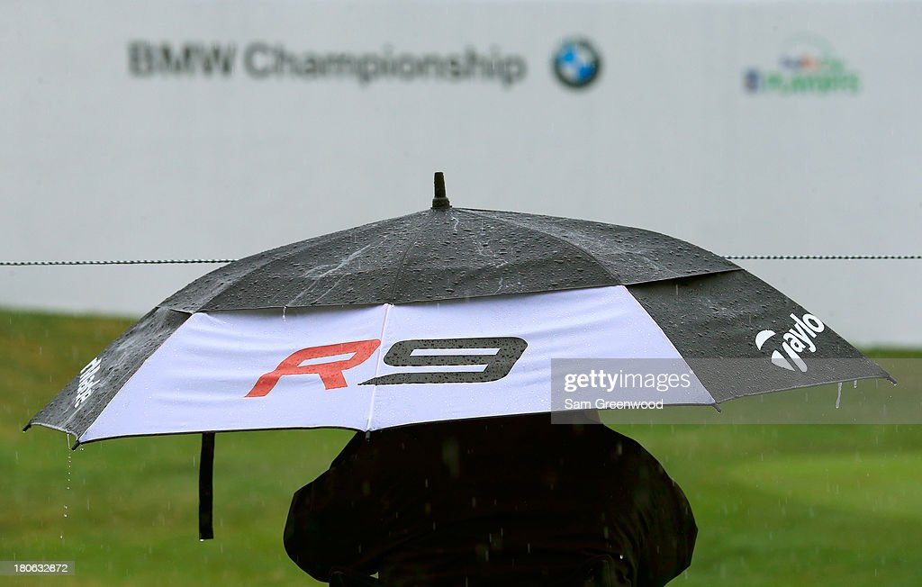 A fan sits in the rain with umbrellas as play is suspended due to inclement weather during the Final Round of the BMW Championship at Conway Farms Golf Club on September 15, 2013 in Lake Forest, Illinois.