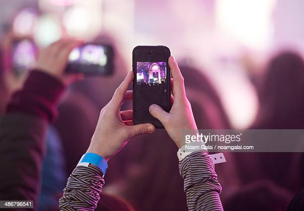 Fan snaps a photo with a phone at a concert