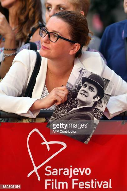 A fan stands at the red carpet with a picture of British actor John Cleese as she waits for his arrival for the 23rd Sarajevo Film Festival late on...