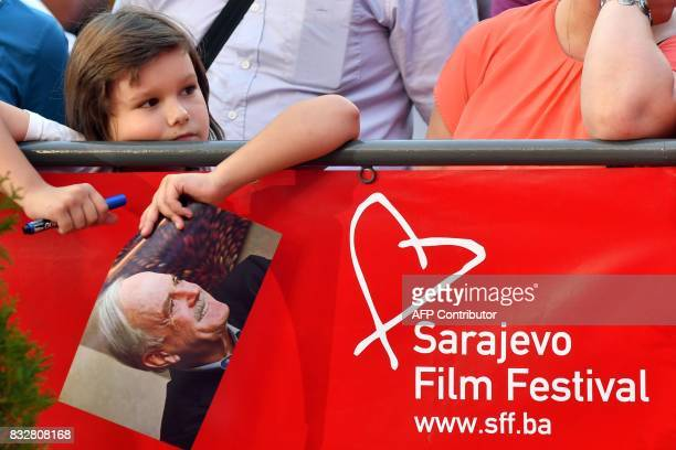 A fan stands at the red carpet with a picture of British actor John Cleese as he waits for his arrival for the 23rd Sarajevo Film Festival late on...