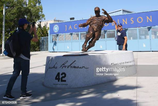 A fan takes a photo of her friend standing next to the Jackie Robinson statue prior the MLB game between the Colorado Rockies and the Los Angeles...