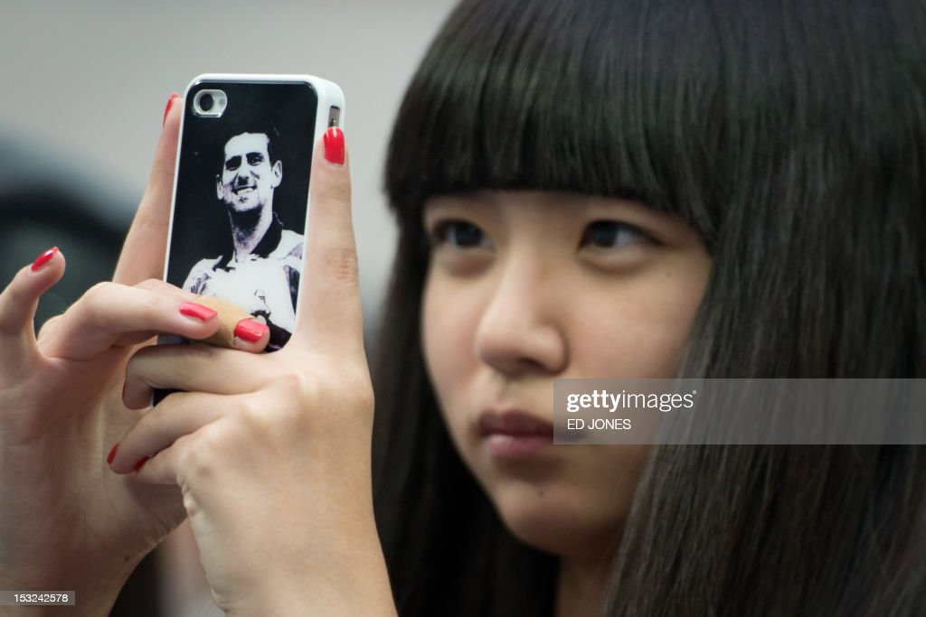 A fan takes a photo using a smartphone featuring an image of Novak Djokovic of Serbia during his tennis match against Michael Berrer of Germany at the China Open tennis tournament at the National Tennis Center in Beijing on October 2, 2012. Djokovic won 6-1, 6-7, 6-2. AFP PHOTO / Ed Jones