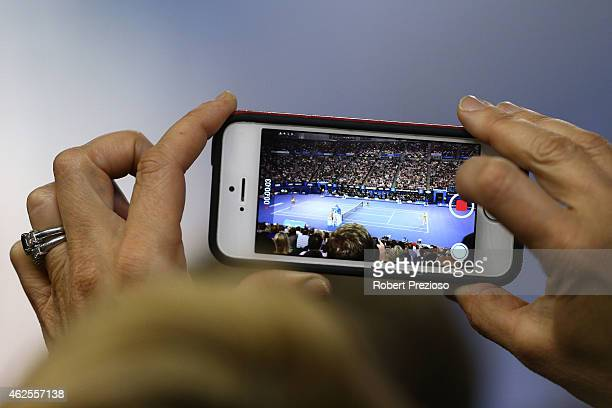 A fan takes a photo with an iPhone at Rod Laver Arena during day 13 of the 2015 Australian Open at Melbourne Park on January 31 2015 in Melbourne...