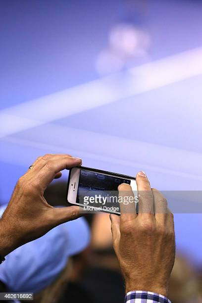 A fan takes a photo with an iPhone at Rod Laver Arena during day 14 of the 2015 Australian Open at Melbourne Park on February 1 2015 in Melbourne...