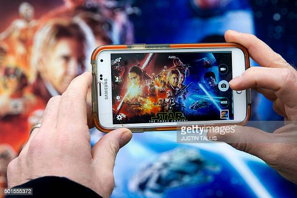 A fan takes a photograph of the poster for 'Star Wars The Force Awakens' before its European Premiere in central London on December 16 2015 Ever...