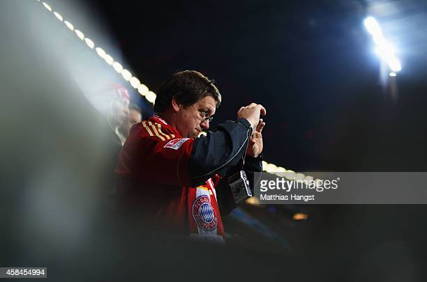 A fan takes a photograph prior to the UEFA Champions League Group E match between FC Bayern Munchen and AS Roma at Allianz Arena on November 5 2014...