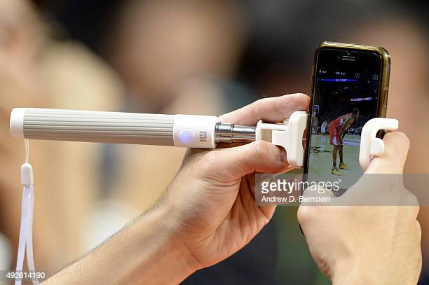 A fan takes a picture of Chris Paul of the Los Angeles Clippers during a game between the Los Angeles Clippers and the Charlotte Hornets as part of...