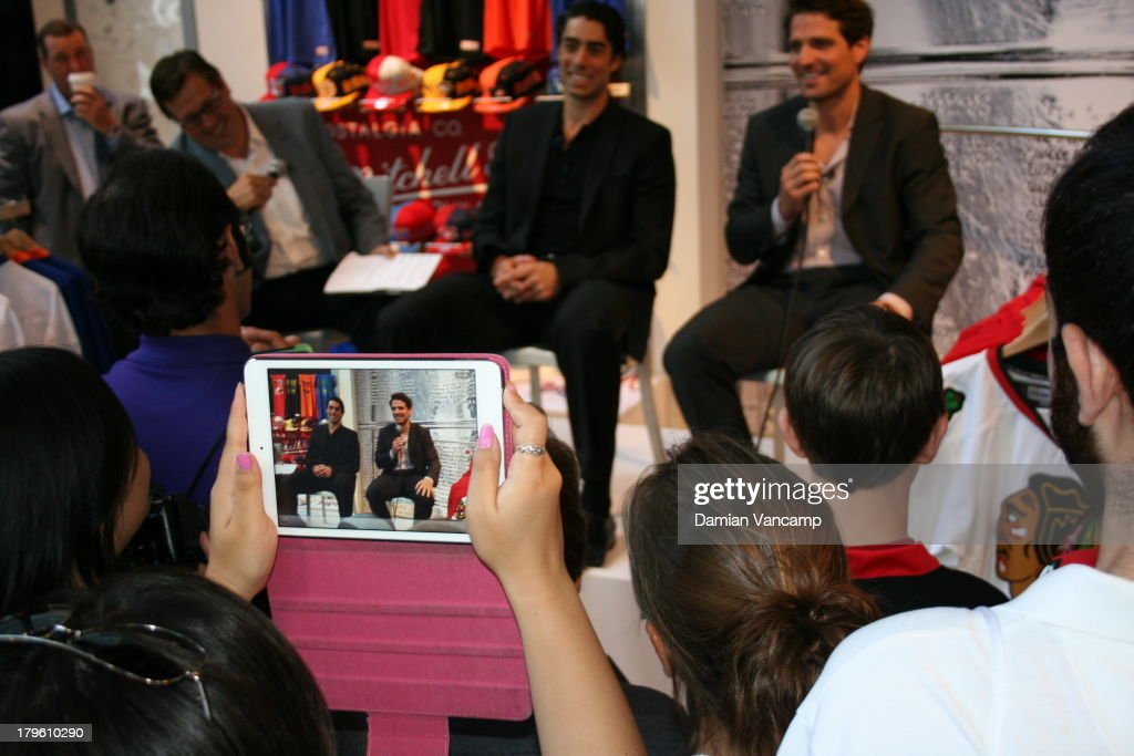 A fan takes a picture on her tablet as EJ Hradek of NHL Studios USA interviews Matt Moulson #26 of the New York Islanders and Patrick Sharp #26 of the Chicago Blackhawks live in front of fans at the NHL Store Powered by Reebok on September 5, 2013 in New York City.