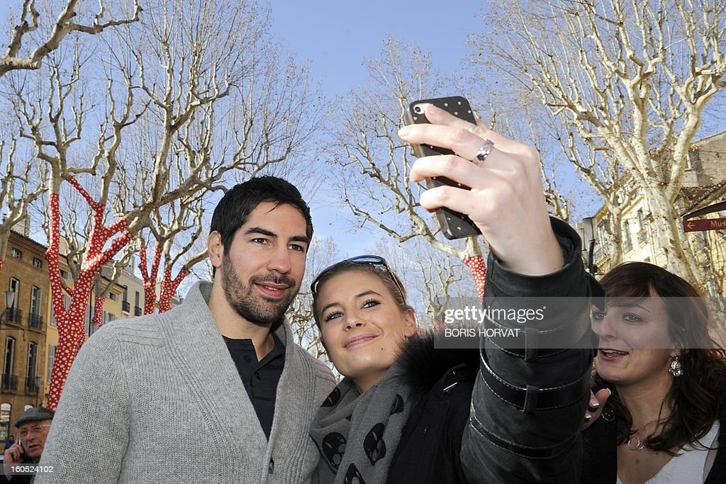 A fan takes a picture with Handball club of Aix-en-Provence (PAUC) newly recruted player Nikola Karabatic (L) after he signed his contract, on February 2, 2013 in Aix-en-Provence, southern France. AFP PHOTO / BORIS HORVAT