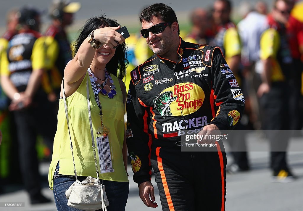 A fan takes a self portrait with Tony Stewart, driver of the #14 Bass Pro Shops / Ducks Unlimited Chevrolet, during qualifying for the NASCAR Sprint Cup Series Coke Zero 400 at Daytona International Speedway on July 5, 2013 in Daytona Beach, Florida.