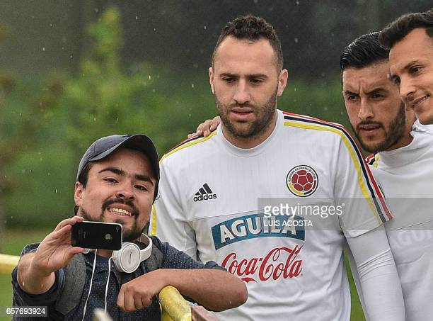 A fan takes a selfie with Colombia's goalkeeper David Ospina and players David Gonzalez and Camilo Vargas before a training session at the Colombian...