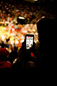 Unrecognizable fan takes a photo using his smart phone during a sports event inside a large sports stadium or auditorium.