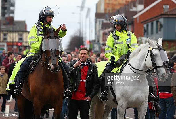 A fan talks to mounted police prior to the Barclays Premier League match between Manchester United and Liverpool at Old Trafford on March 16 2014 in...