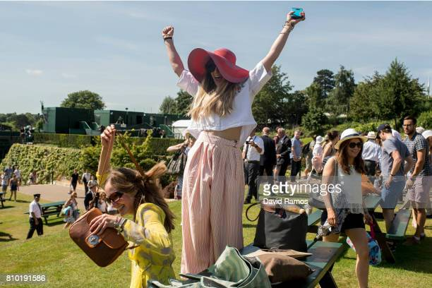 A fan tennis fan celebrates as she gets a bench on Murray Mound ahead of day five of the Wimbledon Lawn Tennis Championships at the All England Lawn...