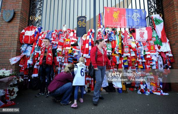 A fan ties a scarf to the Shankly Gates at Anfield before the Hillsborough 25th Anniversary Memorial Service