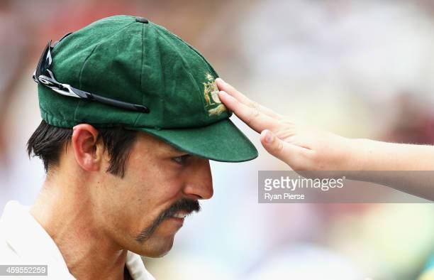 A fan touches the Baggy Green Cap of Mitchell Johnson of Australia as he signs autographs on the boundary during day three of the Fourth Ashes Test...