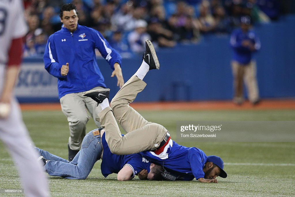 A fan trespassing is tackled by security during the Boston Red Sox MLB game action against the Toronto Blue Jays on April 7, 2013 at Rogers Centre in Toronto, Ontario, Canada.