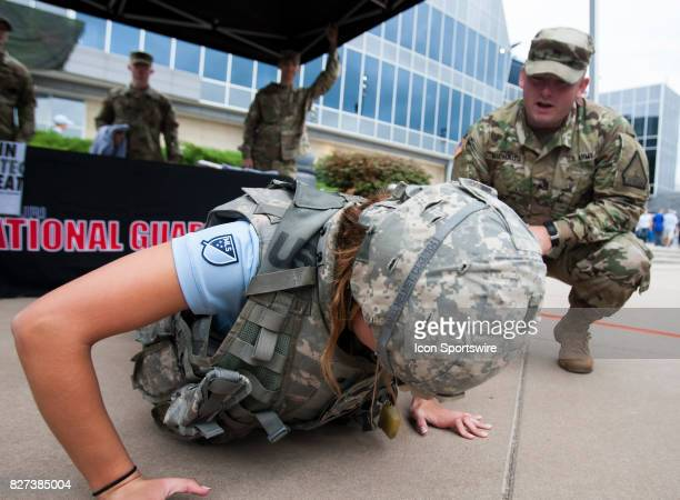A fan tries her hand at pushups while wearing military gear during Military Appreciation day before the match between Sporting Kansas City and...