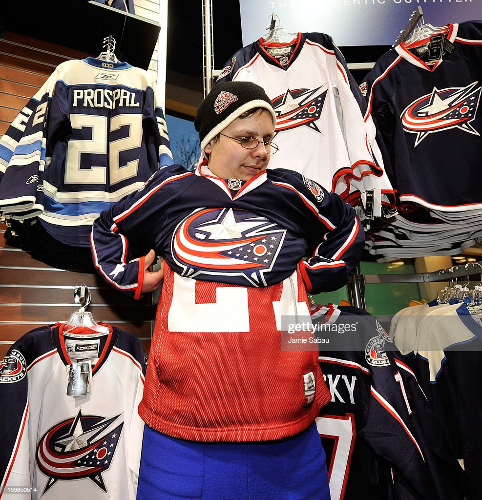A fan tries on a Columbus Blue Jackets jersey in the team store before the Blue Jackets' home opener against the Detroit Red Wings on January 21, 2013 at Nationwide Arena in Columbus, Ohio.