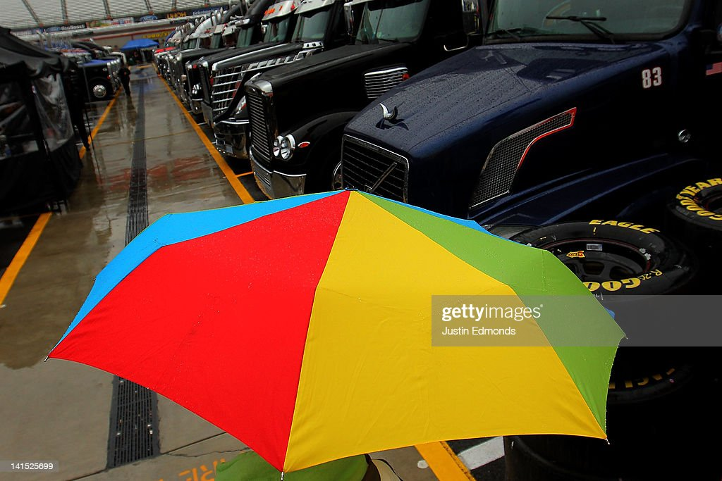 A fan uses an umbrella for rain protection as they walk between the haulers prior to the NASCAR Sprint Cup Series Food City 500 at Bristol Motor Speedway on March 18, 2012 in Bristol, Tennessee.
