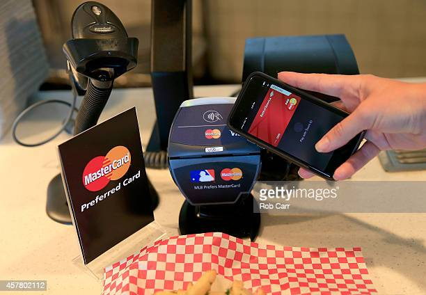 A fan uses MasterCard with Apple Pay to pay for garlic fries before Game Three of the 2014 World Series at ATT Park on October 24 2014 in San...
